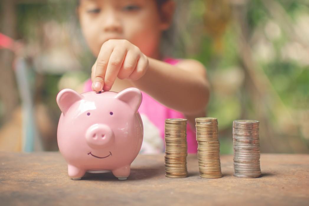 photo d'une petite fille mettant de l'argent dans sa tirelire cochon