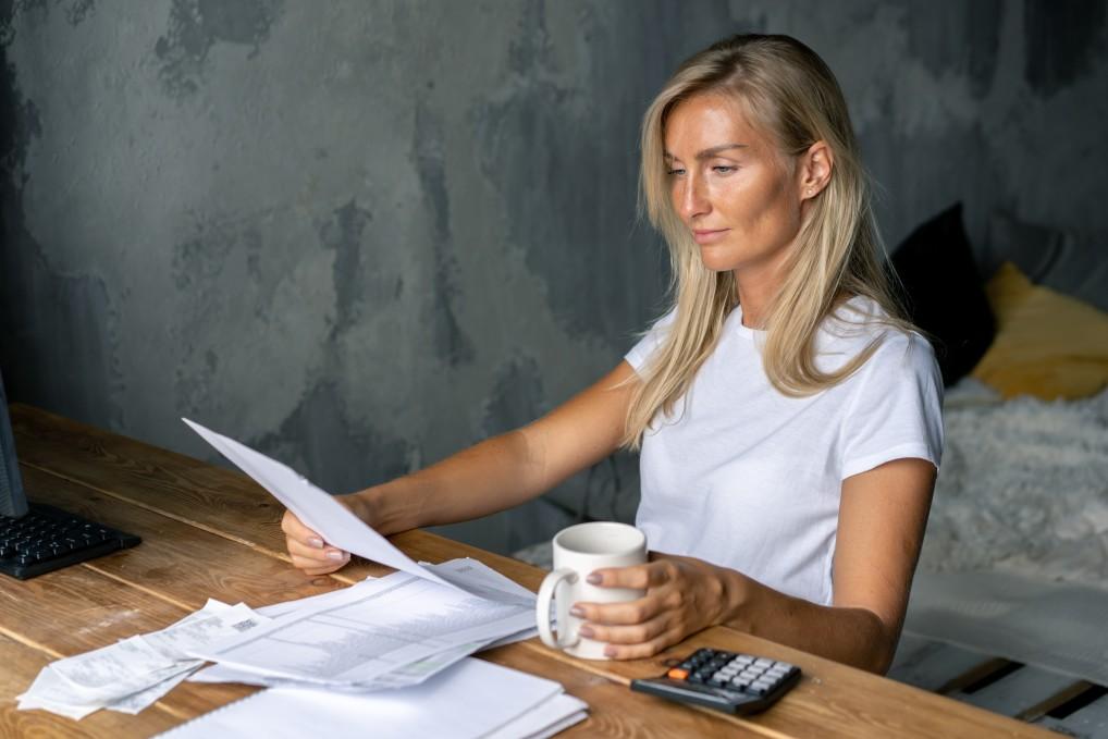 Photo d'une femme assise regardant ses documents
